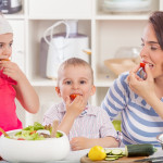 Happy young family preparing and eating vegetable salad